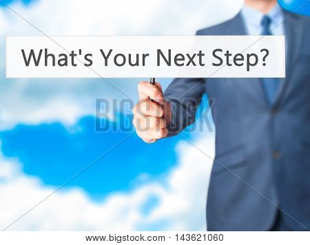 What's Your Next Step? - Businessman Hand Holding Sign