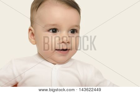 Cute baby boy looking surprised. Adorable baby portrait looking curious isolated on white.