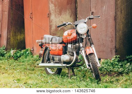 Minsk, Belarus - September 22, 2013: Old Red Motor Cycle Parked On Green Grass Yard. Vintage Generic Motorcycle Motorbike In Countryside On Rusty Background