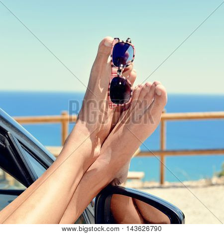 closeup of a young caucasian man who is relaxing in a car near the ocean, with a pair of sunglasses hanging of his bare feet poking out of the window