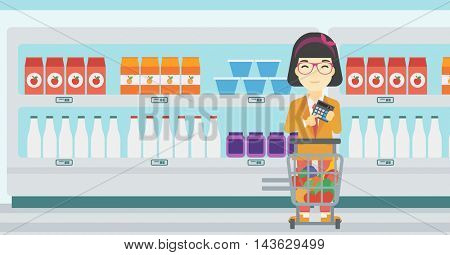 An asian young woman at the supermarket with calculator and supermarket trolley full with products. Woman checking prices with calculator. Vector flat design illustration. Horizontal layout.