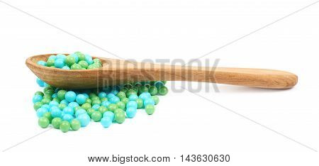 Pile of blue and green sugar candy sprinkle balls with a wooden spoon over it, composition isolated over the white background