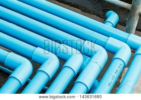 Water valve connected to a PVC pipe, blue water.