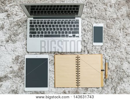 Closeup brown note book with line in page brown pen computer notebook tablet and smart phone on gray fabric capet textured background in top view in work concept