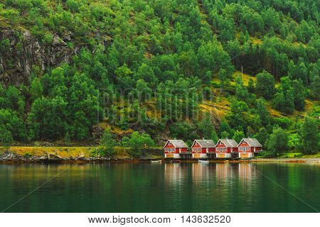 Red Wooden Docks In Small Tourist Town Of Flam On Western Side Of Norway Deep In Fjords. Forest Background