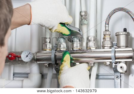 Worker fixing heating system, close up photo.