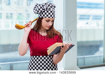 Young housewife referring to recipe book