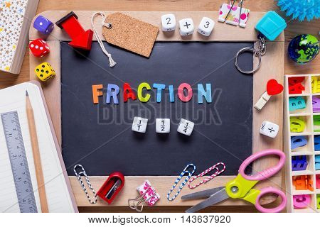 Small blackboard surrounded with various stationary with Fraction word in the middle on wood background
