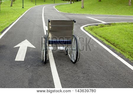 Wheelchair on the road in the park. Encouragement for the sick