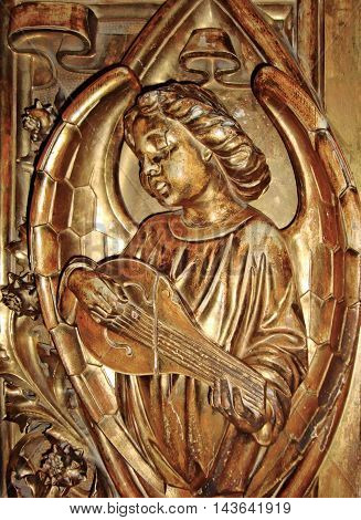 An angel playing a musical instrument. The figure, bas relief of the angel with the lute is made of wood and covered with gold leaf.