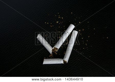 broken cigarette on black leather texture for anti smoking event