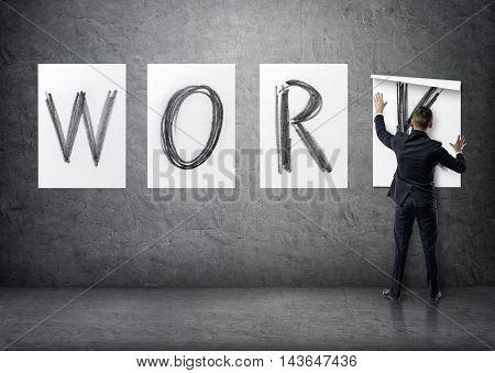 Businessman putting up posters with letters on a concrete wall that form a 'work' word. Business staff. Office clothes. Succesful management.