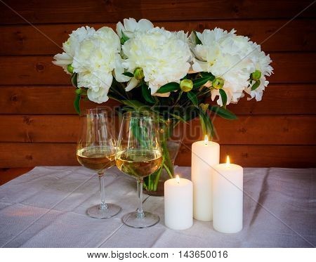 Beautiful bouquet of white peonies glasses of wine and candles