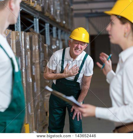Older warehouseman having a painful infarction at work