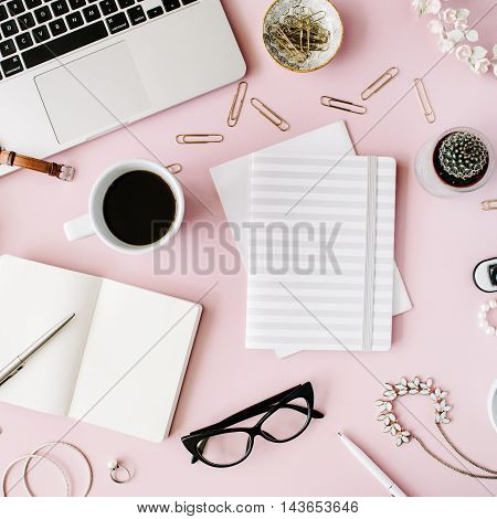 Flat lay, top view office table desk. feminine desk workspace with succulent, laptop, glasses, diary and golden clips on pink background.