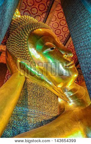 Closed up reclining Buddha Image at Wat Pho Bangkok Thailand. Generally in Thailand any kind of art decorated in Buddhist church temple pavilion temple hall monk's house etc. created with money donated by people to hire artist. They are public domain or t