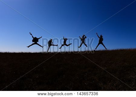 They are jumping while walking on a hill of Doi Mon jong the mountain in Chiang Mai, Thailand.