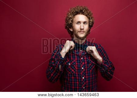 Portrait of surprised curly-haired man in checked shirt and bow-tie on red background. Isolate