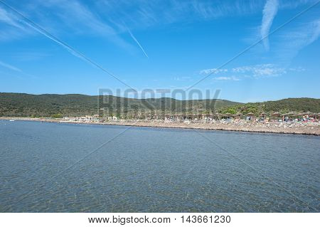 Sea coastline and beach resort full of people under summer blue sky and green hills in background