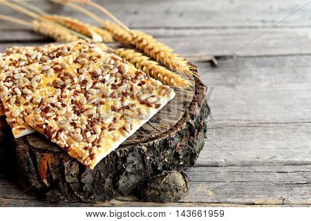 Healthy cookies with sunflower seeds, flax seeds and sesame seeds and spikelets of wheat on old wooden background. Vegan cookies snack