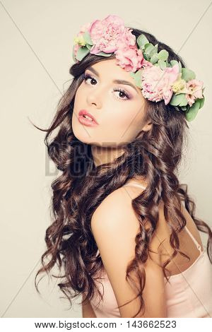 Beautiful Young Woman with Summer Pink Peony Flowers. Long Curly Hair and Fashion Makeup. Beauty Girl with Flowers Hairstyle