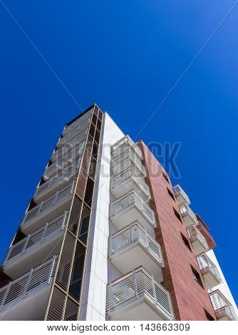 Modern residential building facade with balconies. Bottom view.