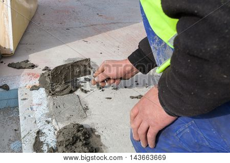 Worker use spatula for plastering a floor
