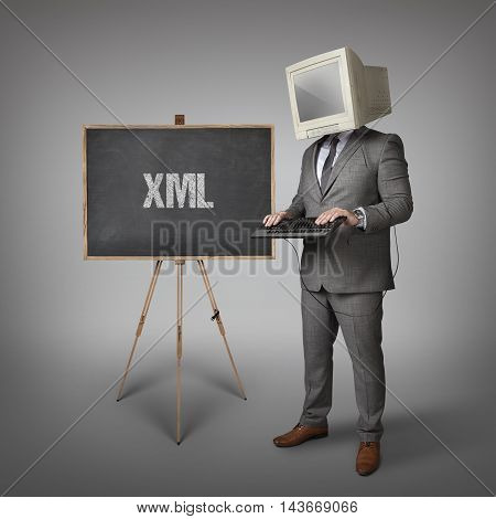 XML text on blackboard and computer monitor on businessman head