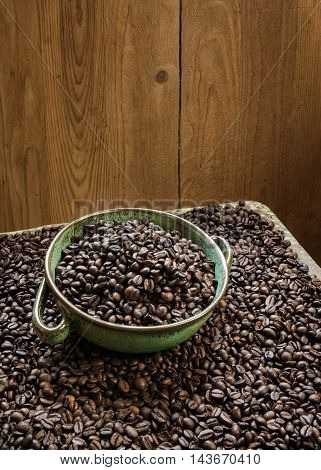 Fresh coffee beans in bowl on wooden background