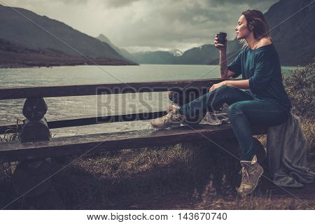 Confident woman with cup of coffee or tea sitting on a banch near the wild lake, with mountains on the background.