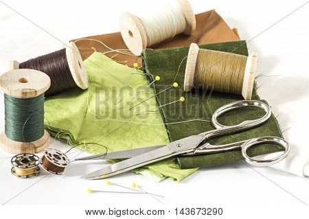 Threads, scissors and fabrics in Brown and green