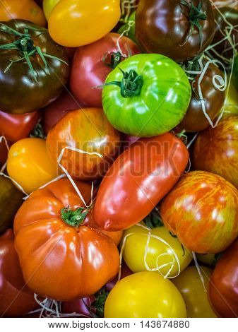 Fresh red, brown, yellow and green ripe tomatoes in wooden baskets on sale on a farmers Borough Market in London