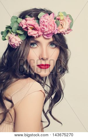 Beauty Girl with Flowers Hairstyle. Beautiful Young Woman Portrait with Summer Pink Pione Flowers. Long Permed Curly Hair and Fashion Makeup