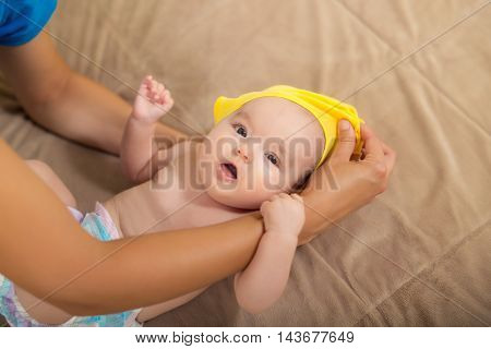 Young woman dressing a baby girl on the bad
