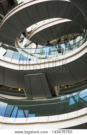 LONDON, UK - SEPTEMBER 19, 2016: Spiral staircases of London City Hall with walking people. Modern architectural structure
