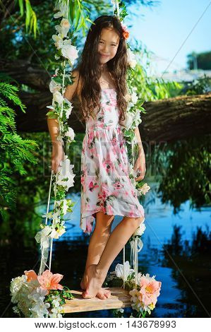 Girl on home made tree swing over river. swing decorated with flowers. Girl wearing a summer dress and standing on a swing over water.