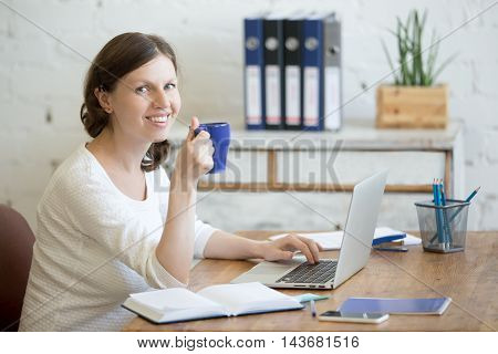 Young Business Woman Drinking Coffee At Workplace