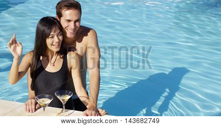 Loving couple smooching at swimming pool