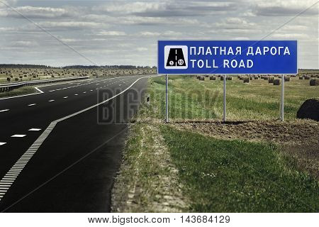 Warning sign of the toll road on the highway. Empty track, no one.