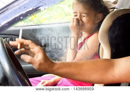 Stop smoking for children. Father smoking a cigarette and the child choking of smoke in a car