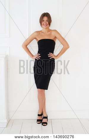 A cheerful woman with red lips and in a black dress shows a beautiful way to pose with hands on the hips and crossed legs