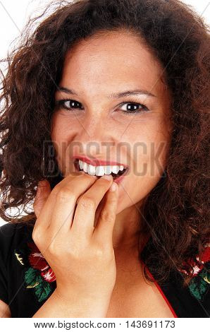 A closeup of the face of a young woman with curly brunette hair biting her finger nail.