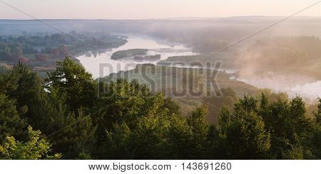 Summer landscape with the beautiful river and morning fog. Deciduous forest on a hill. Ros river, Ukraine, Europe