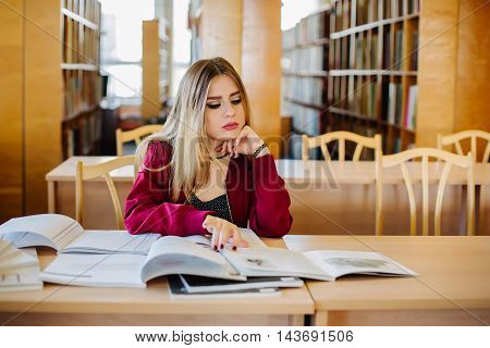 Bored and tired attractive female student sitting at desk in old university library preparing for exam and reading books. Education process.