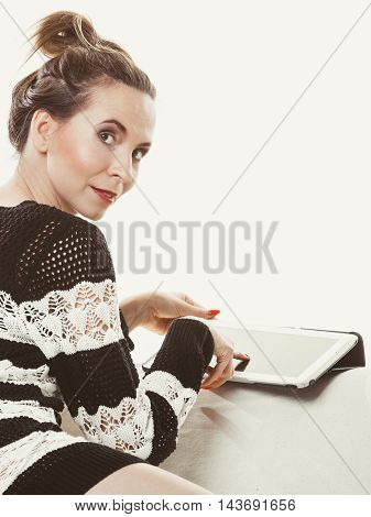 Technology internet concept. Fashion trendy woman sitting with tablet on white couch at home