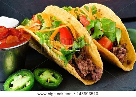 Hard Shelled Tacos With Ground Beef, Lettuce, Tomatoes And Cheese Close Up, On Slate Background