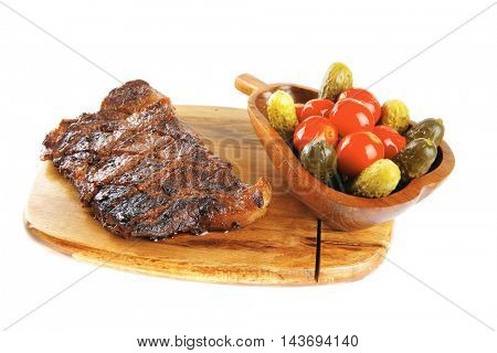 grilled steak entrecote and vegetables on wooden plate isolated over white background