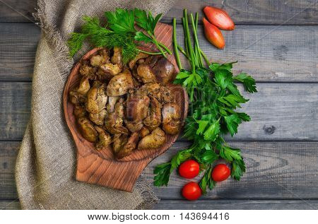 Stewed chicken liver additional ingredients for chicken liver parsley dill cherry tomatoes shallot gray wooden background rustic style top view