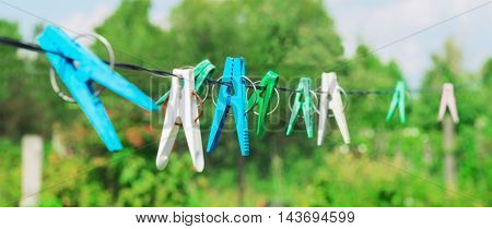 Plastic clothespins laundry hook colorful rope.Village plastic pegs. Three white clothes pins two blue clothespin rope on focus four green clothespins. Summer rural landscape.
