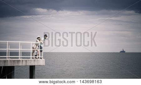 Summer vacation. Loving hipster couple woman and man spending leisure time together walking on sea pier
